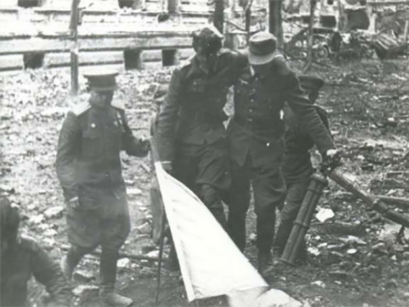 Pięciu niemieckich żołnierzy na gruzach Festung Breslau. Jeden z nich niesie białą flagę.